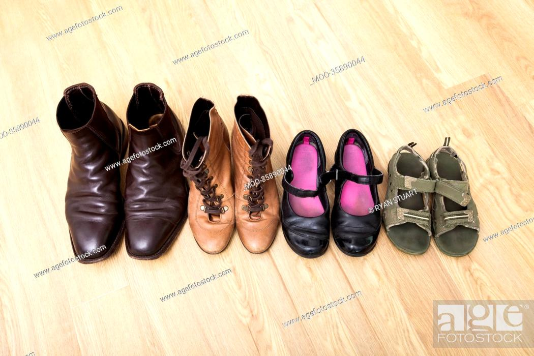 Stock Photo: Family shoes placed in a row on hardwood floor.