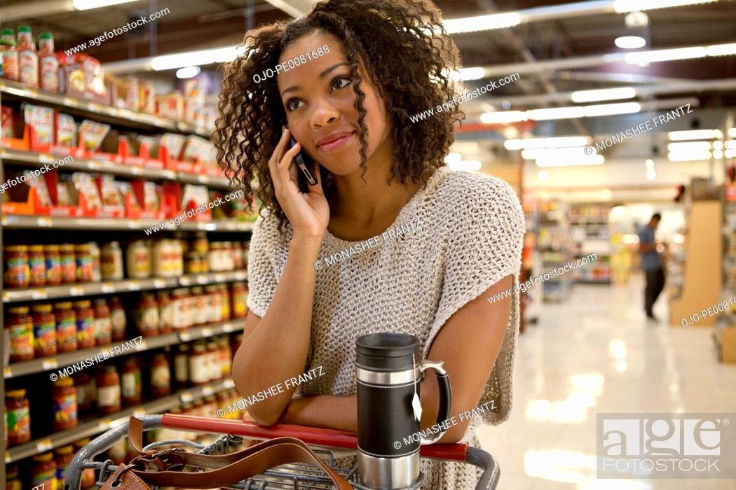 Stock Photo: Woman talking on cell phone in supermarket.