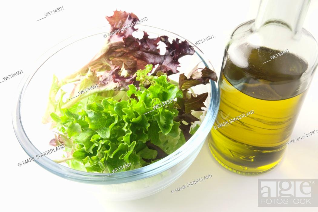 Imagen: Mixed Red and Green Multileaf Lettuce Leaves in a Glass Bowl with Extra Virgin Olive Oil.