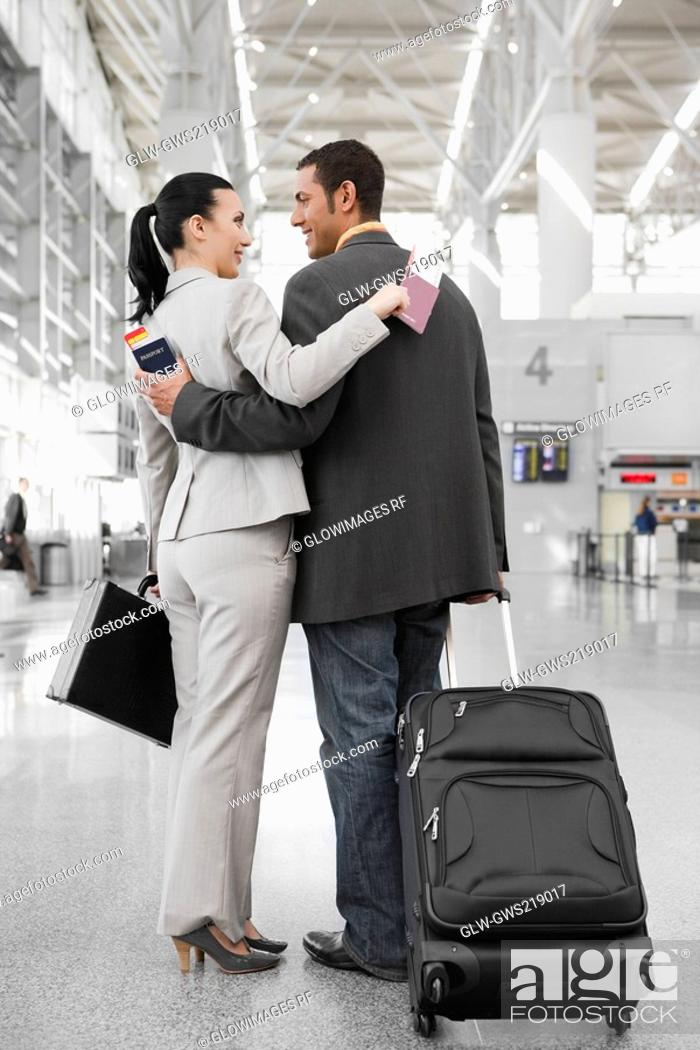 Stock Photo: Businessman and a businesswoman standing at an airport with their arms around each other.