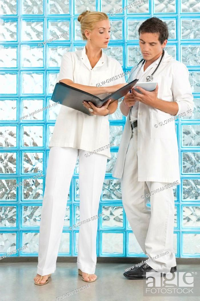 Stock Photo: Female doctor and a male doctor discussing a medical report.