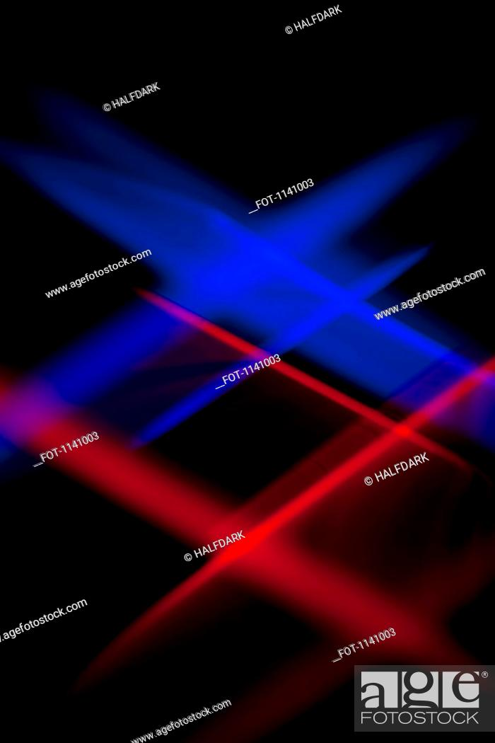 Stock Photo: Blue and red lights crisscrossing against a black background.