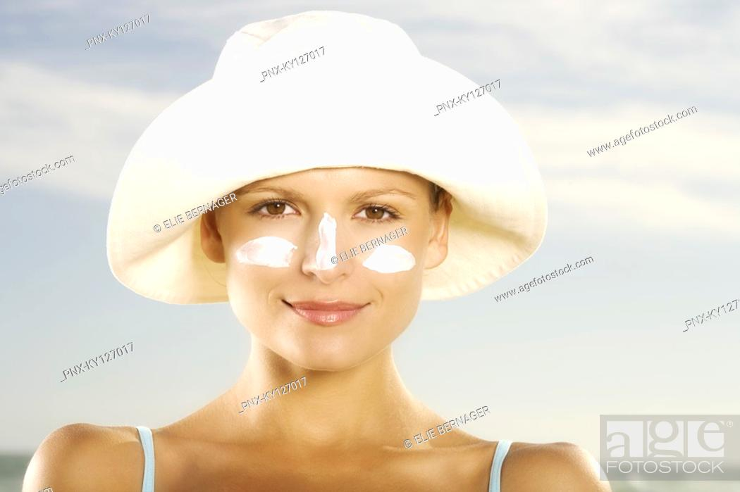 Stock Photo: Portrait of a young woman with sun cream on face.