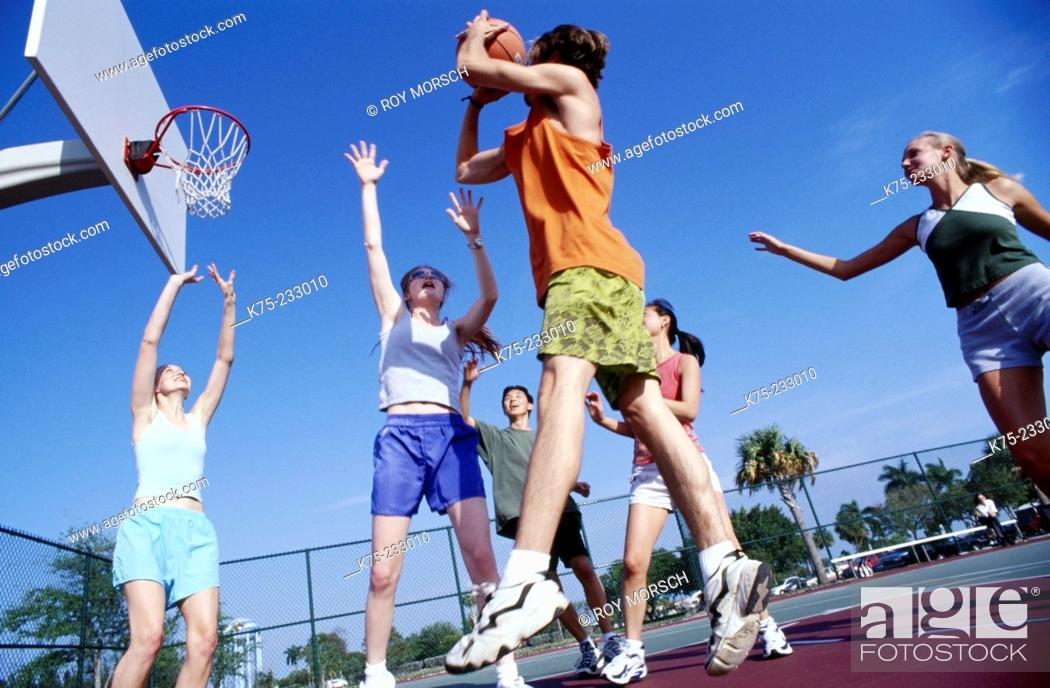 Stock Photo: Girls and guys playing basketball.