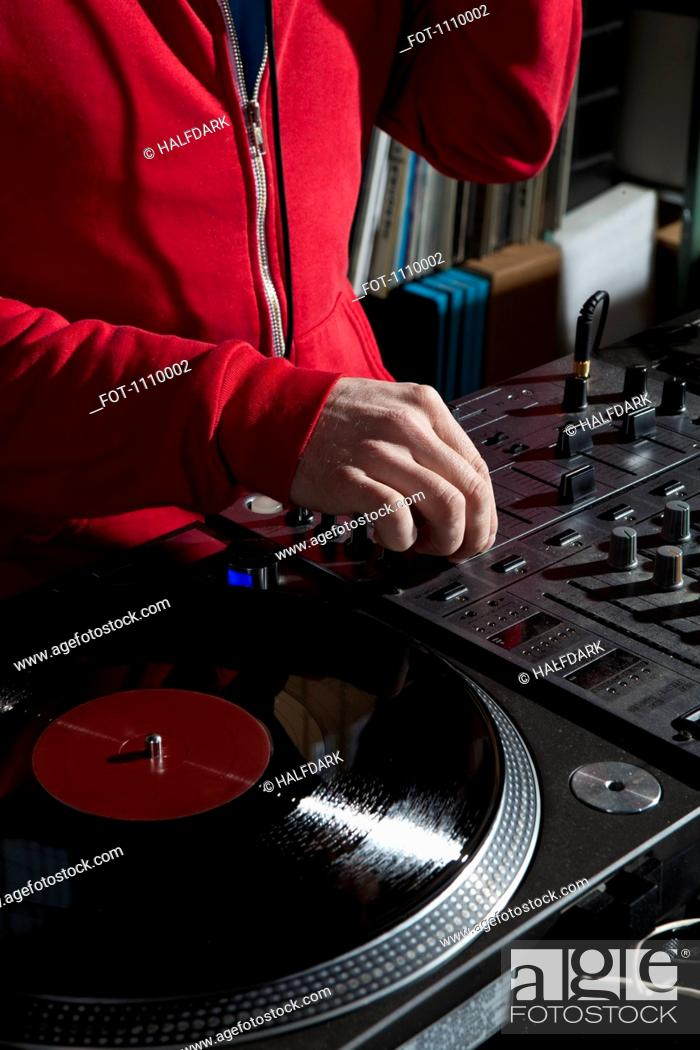 Stock Photo: A DJ adjusting a knob on a sound mixer, detail of hands.