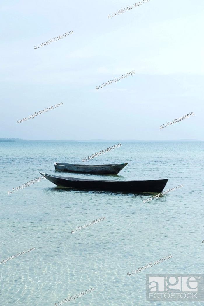 Stock Photo: Pair of empty boats floating next to each other, Zanzibar, Tanzania.