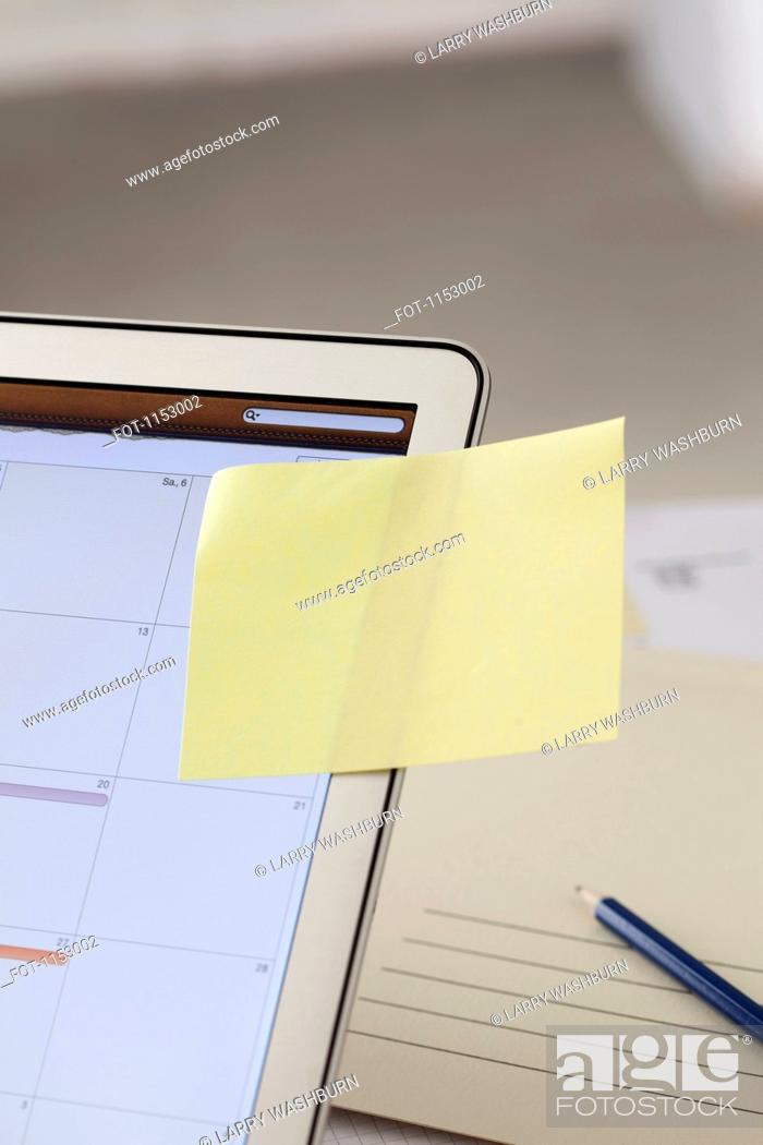 Stock Photo: A blank adhesive note stuck to a laptop screen with a calendar.