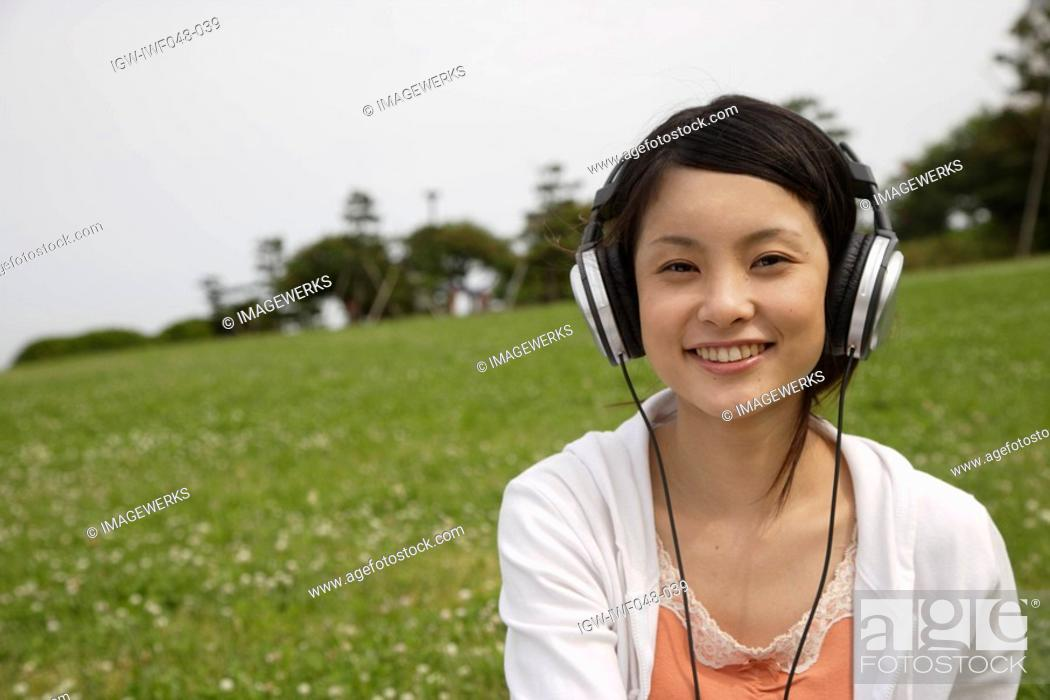 Stock Photo: Portrait of a young woman listening to music.