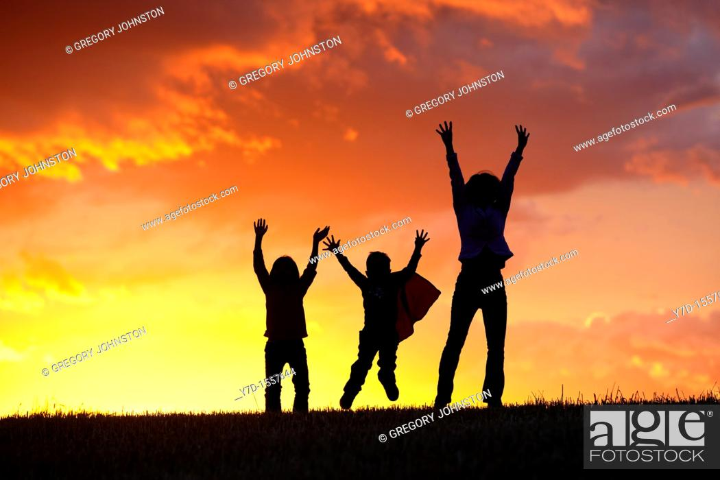 Stock Photo: A woman and her two kids jump for joy at sunset.