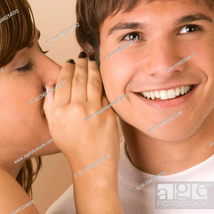 Stock Photo: Side profile of a young woman whispering to a young man.