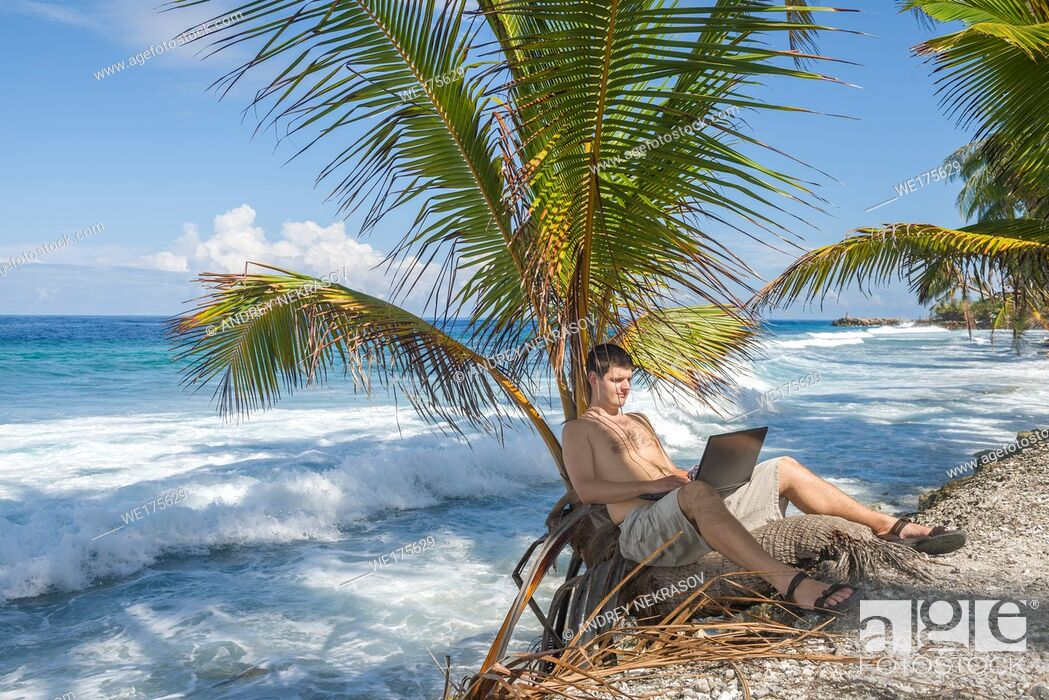 Stock Photo: Man working on the beach. Attractive man with laptop seated in a palm tree on a tropical beach. Young man working on laptop computer on the tropical beach in a.