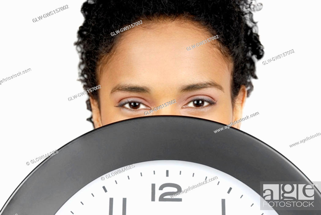 Stock Photo: Portrait of a businesswoman hiding her face behind a clock.