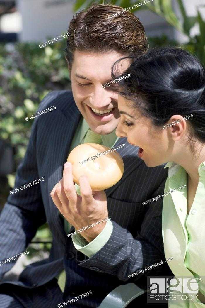 Stock Photo: Businessman feeding a donut to a businesswoman smiling.