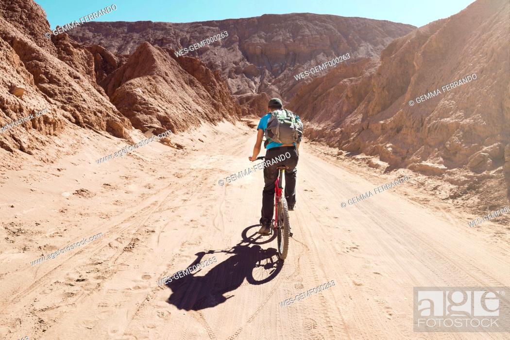 Chile, Man riding a mountain bike through the Valle de la