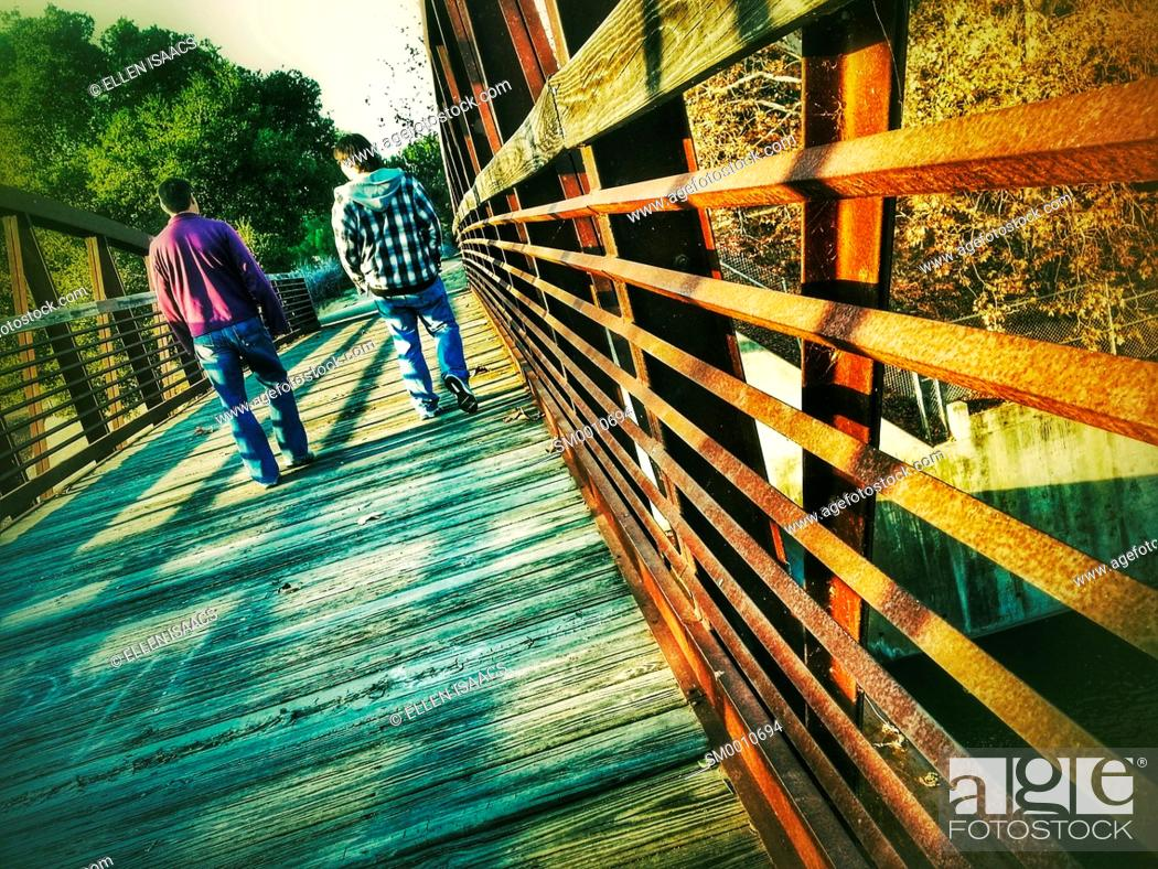 Stock Photo: Two men walking casually into the distance across an iron bridge expressing a feeling of comfortable friendship.