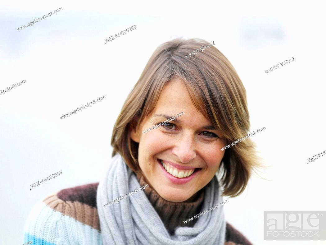 Stock Photo: Germany, Munich, Mature woman near lake, smiling, portrait.