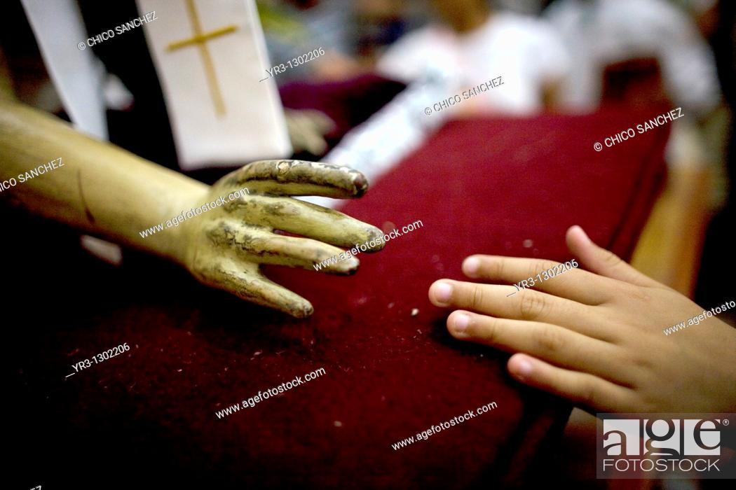 Stock Photo: A woman touches the hand of a statue of Jesus Christ during holy week celebrations in Oaxaca, Mexico, April 10, 2009.
