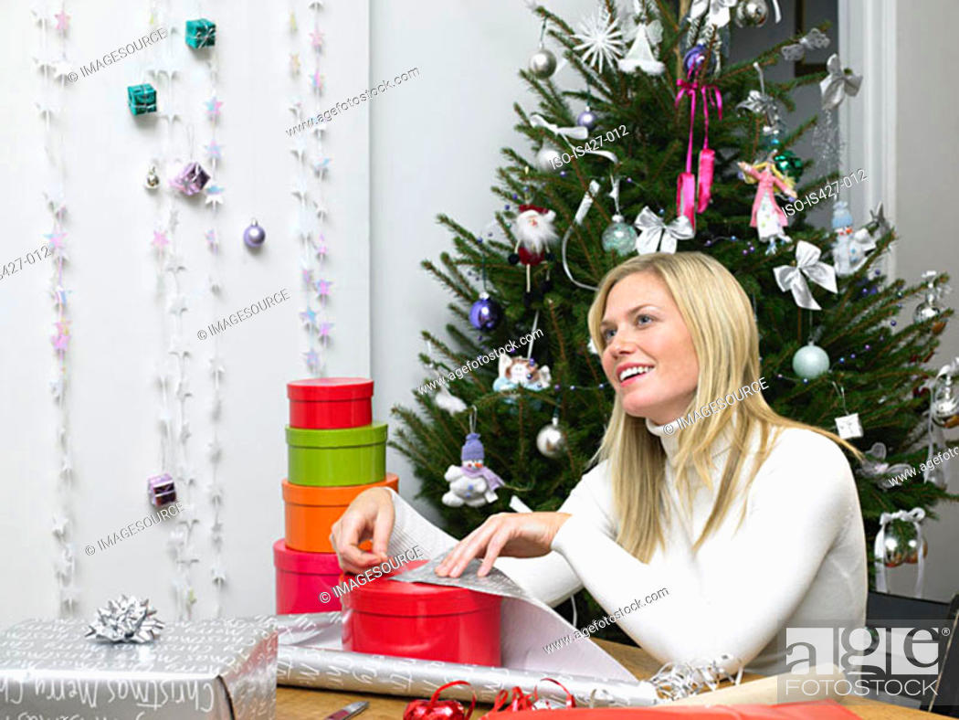 Stock Photo: Woman wrapping christmas gifts.