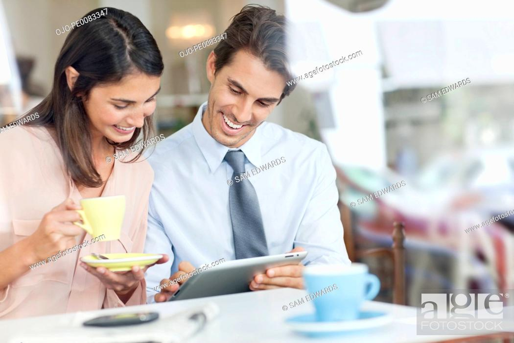Stock Photo: Couple drinking coffee and using digital tablet in café window.