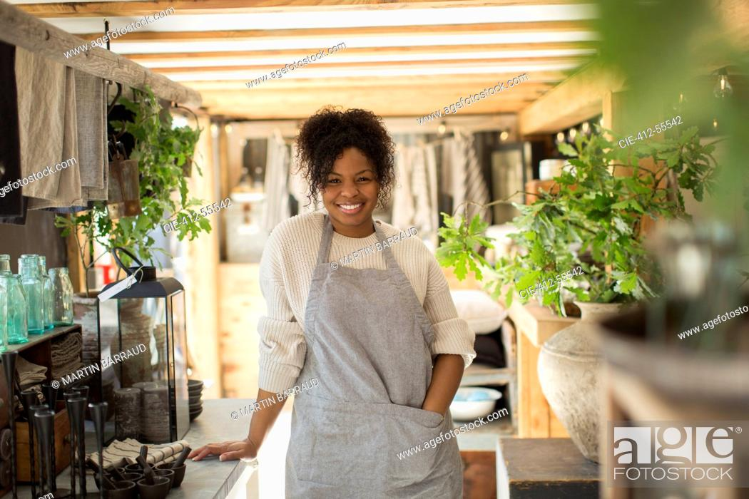 Stock Photo: Portrait happy female shop owner in apron in plant nursery.
