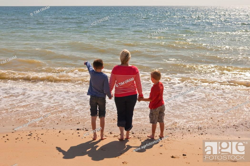 Stock Photo: Mother and two sons stand on a UK beach looking out to sea in the summer.