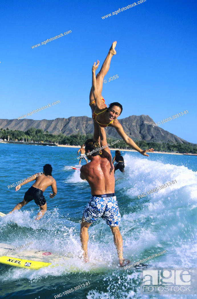 Hawaii Oahu Waikiki Tandem Surfing Man Holds Woman In An