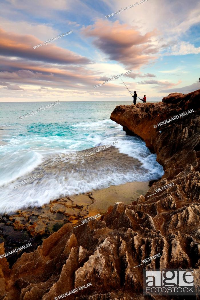 Stock Photo: Landscape photo of two men fishing on the rocks. Arniston/Waenhuiskrans, Western Cape, South Africa.