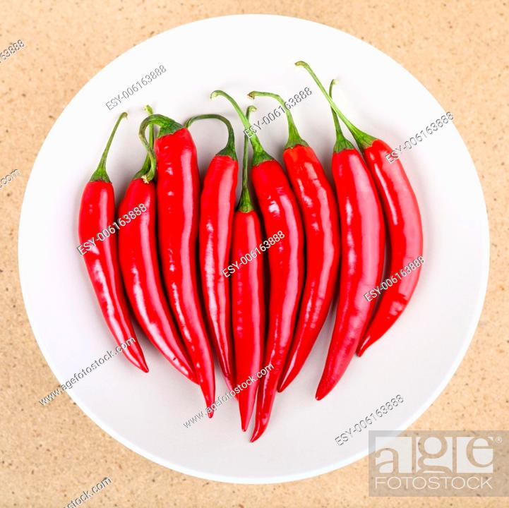 Stock Photo: Plate with fresh raw red hot chili peppers on the table.