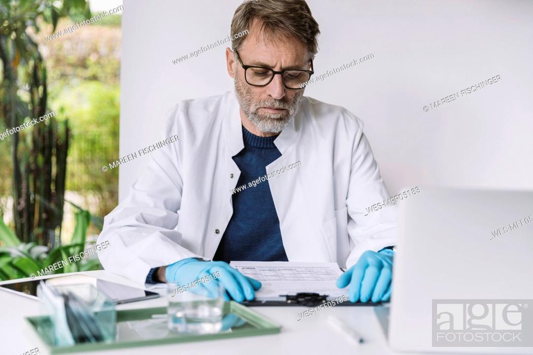 Stock Photo: Scientist reading document at desk.