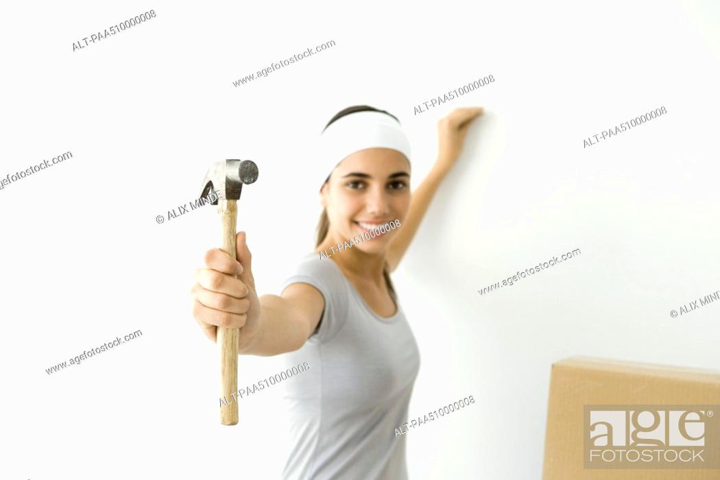 Stock Photo: Teen girl showing hammer to the camera, smiling.