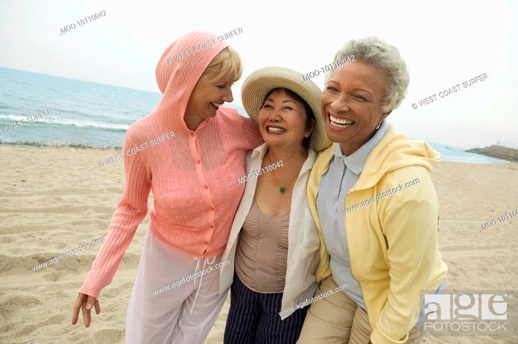 Stock Photo: Female friends walking side by side on beach.