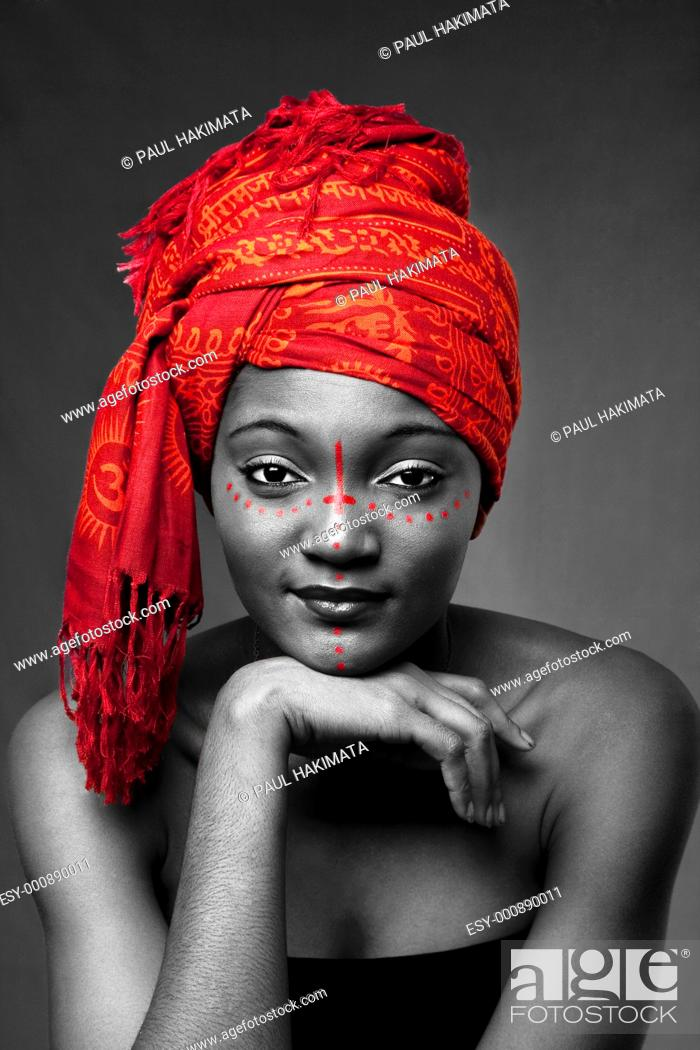 Stock Photo: Beautiful traditional African-American woman wearing a authentic tribal red orange head scarf and red dotted makeup, supporting her chin with hand, isolated.