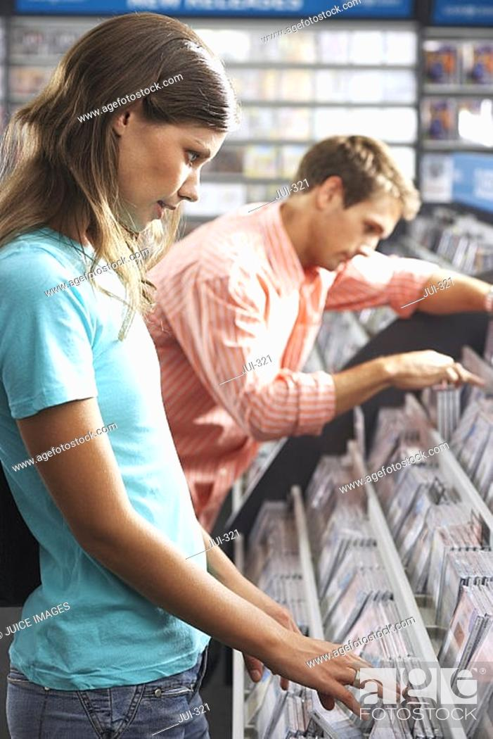 Stock Photo: Young couple sifting through CDs in record shop, side view.