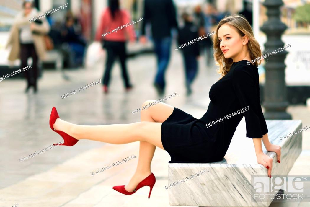 25062cdf993e Stock Photo - Funny blonde woman with beautiful legs in urban background.  Beautiful young girl wearing black elegant dress and red high heels sitting  on a ...