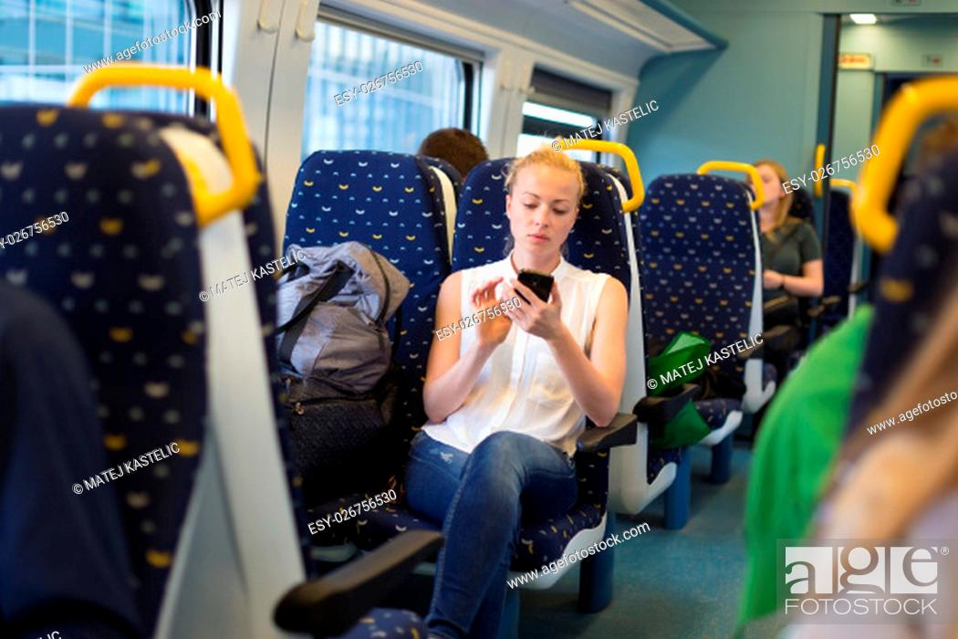 Imagen: Woman workin on smart phone while traveling by train. Business travel concept.