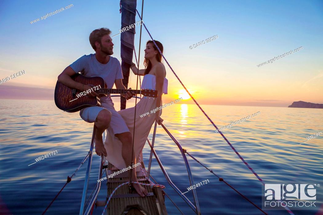 Imagen: Young man playing guitar on sailboat at sunset.