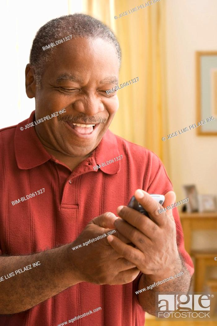 Stock Photo: Senior African man looking at cell phone.