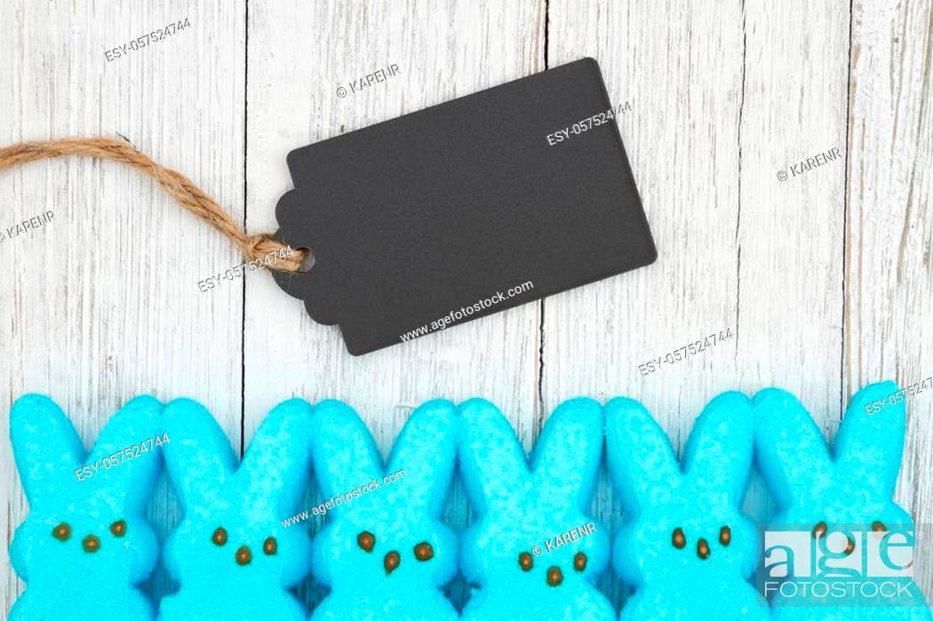 Stock Photo: Blue candy bunnies with gift tag on weathered whitewash textured wood background with copy space for your Easter message.