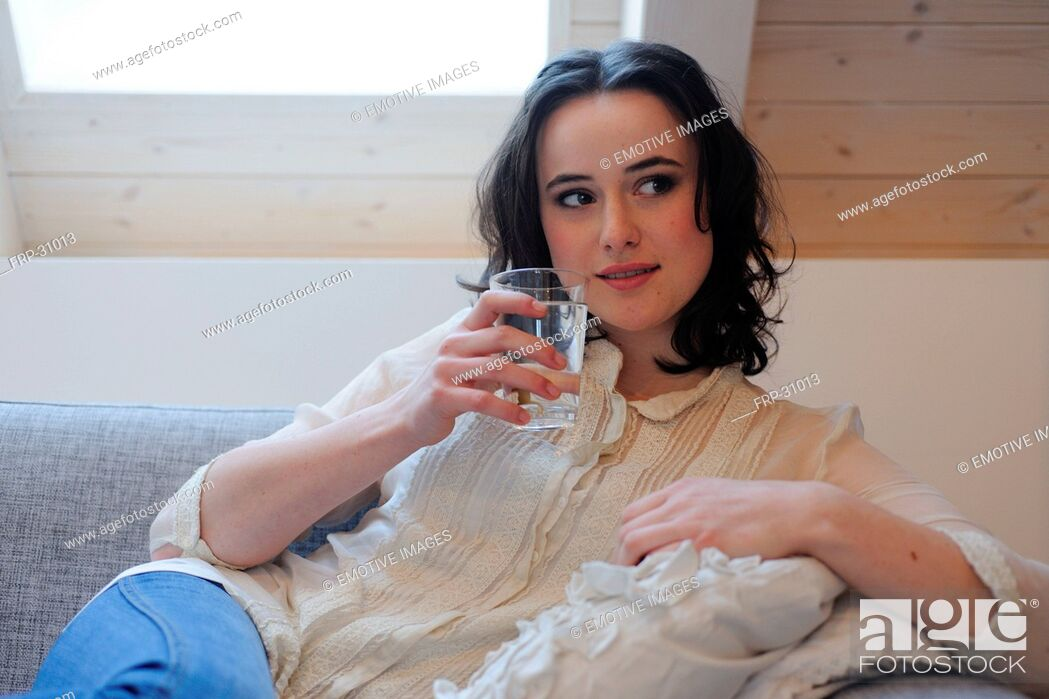 Imagen: Young woman on couch drinking glass of water.