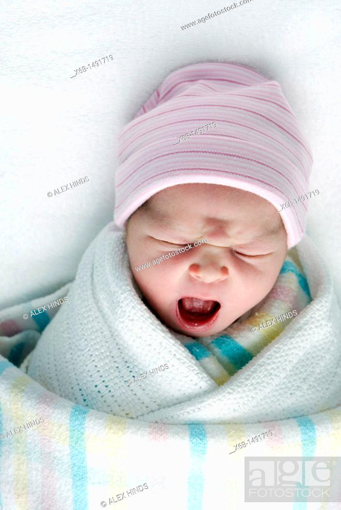 Stock Photo: A newborn baby swaddled in blankets.