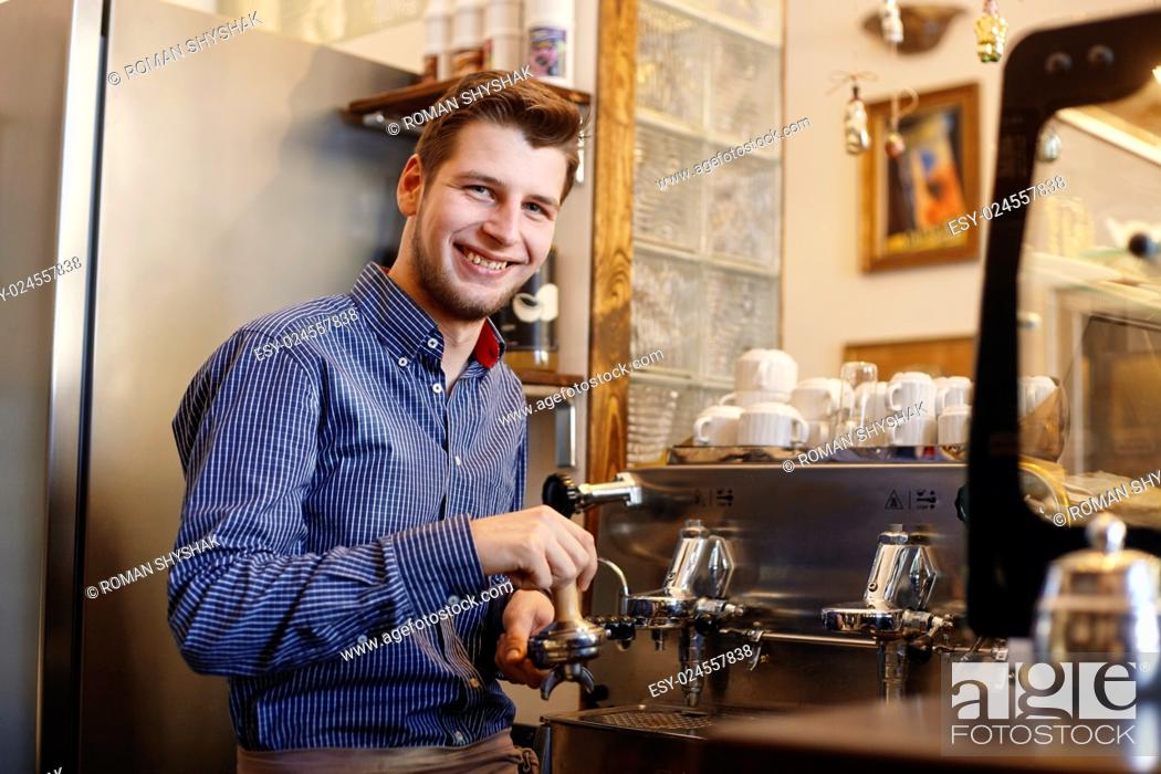 Stock Photo: Young smiling man is making coffee with a coffee machine.