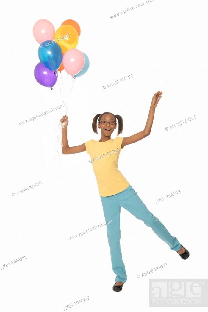 Stock Photo: Ten year old girl holding balloons.