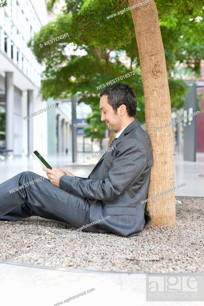 Stock Photo: Germany, Leipzig, Businessman sitting at tree and using digital tablet.