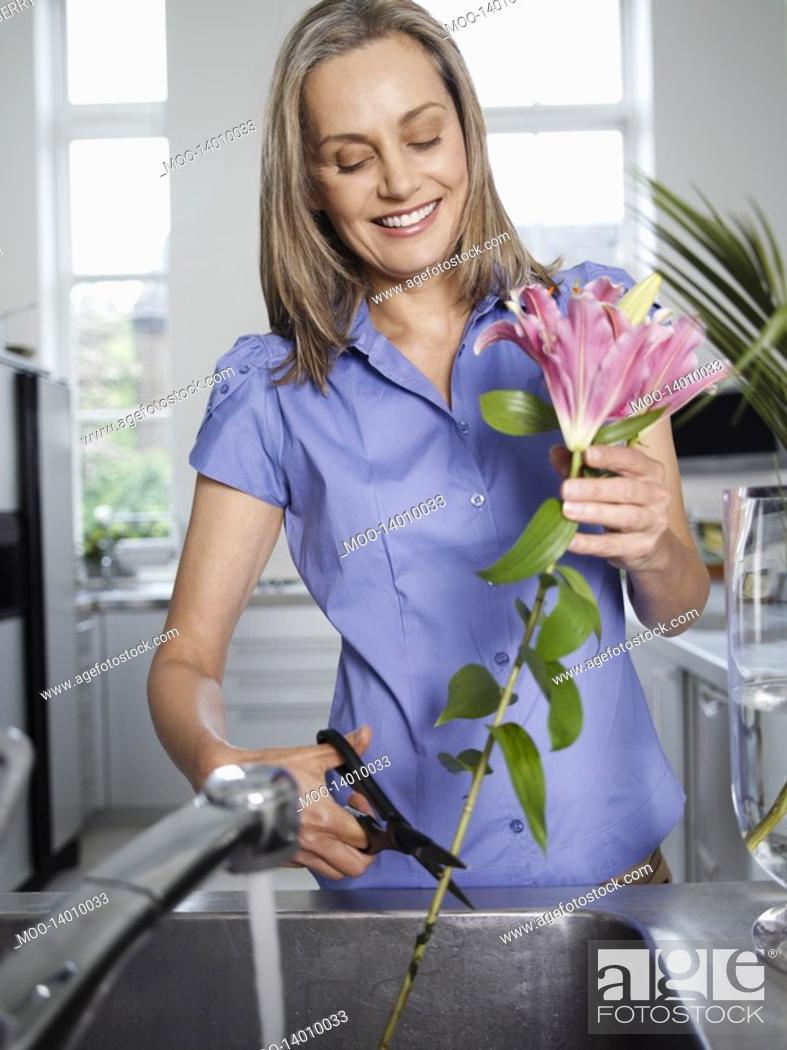 Stock Photo: Mid-adult woman rinsing and cutting flowers in kitchen sink.