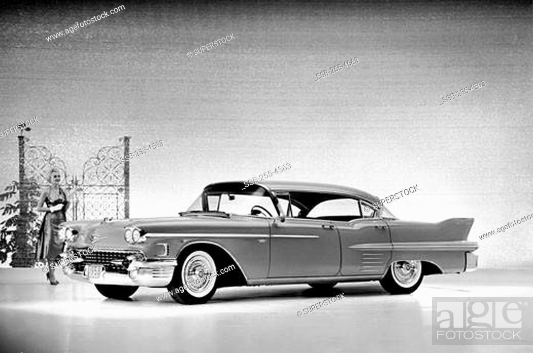 Stock Photo: Woman walking behind a 1958 Cadillac Series 62 Sedan.