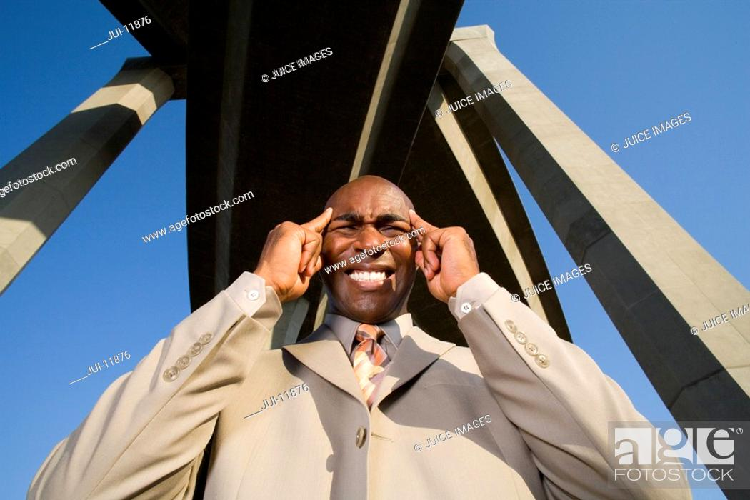 Stock Photo: Businessman with hands to head beneath overpasses, low angle view.