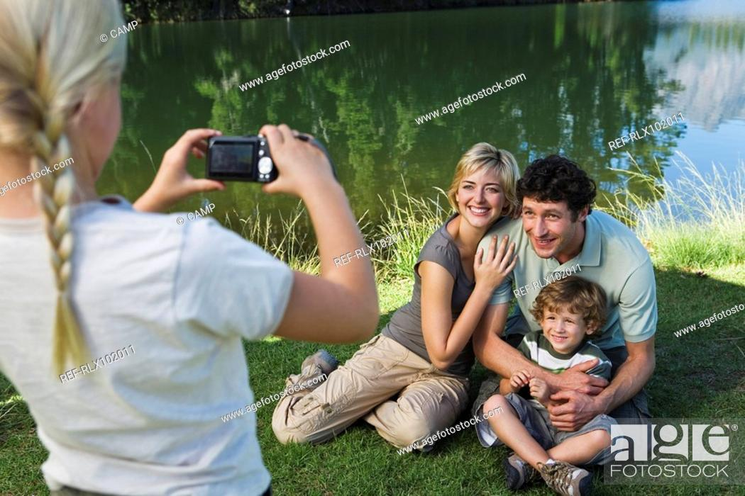 Stock Photo: Girl photographing family outdoors, family posing for picture.