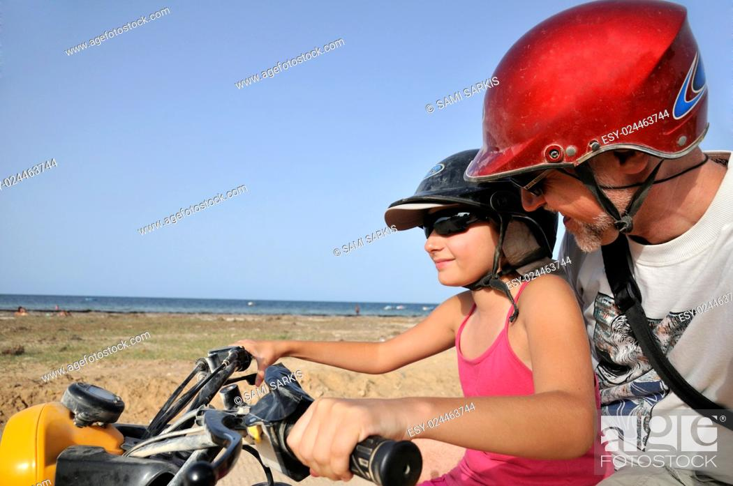 Imagen: Girl (10) driving an ATV with her dad by seacoast, Djerba Island, Tunisia.