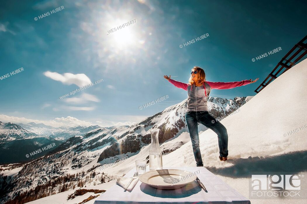 Imagen: Young woman standing in the mountains, with laid table in foreground.