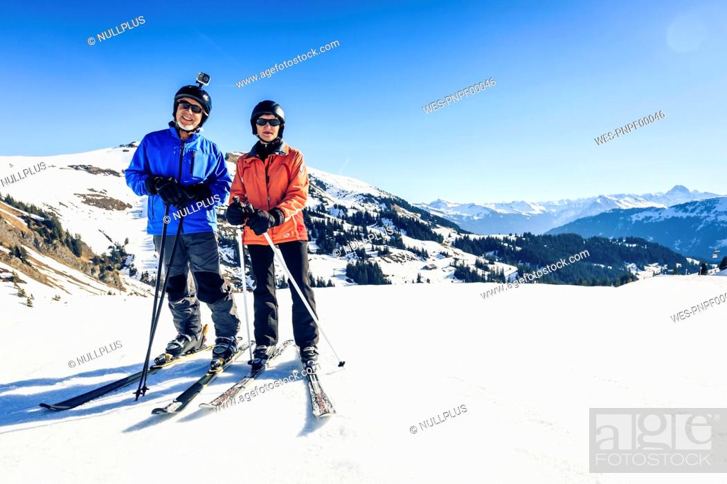 Stock Photo: Austria, Damuels, couple with action cam skiing in winter landscape.